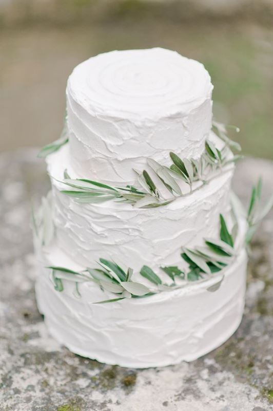 a textural white wedding cake with olive greenery is ideal for a Tuscany wedding