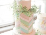 a quirky wedding cake in blush with colorful chevron detailing and lots of greenery for a bright spring or summer wedding
