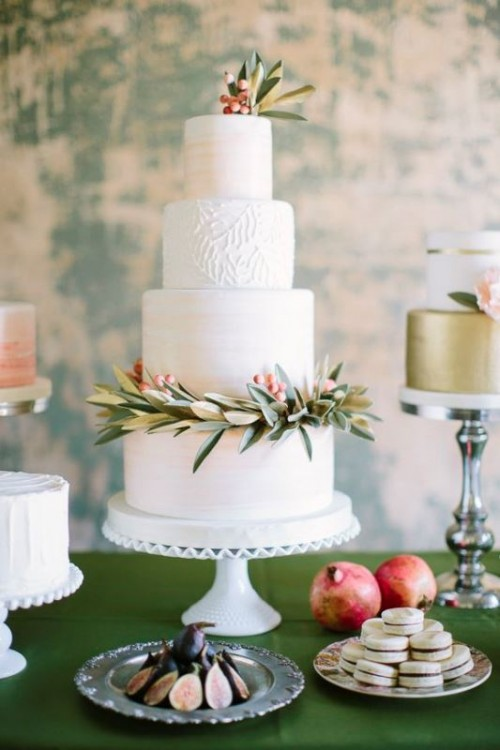 a textural neutral wedding cake with patterns with greenery and bright berries for a Christmas or winter wedding