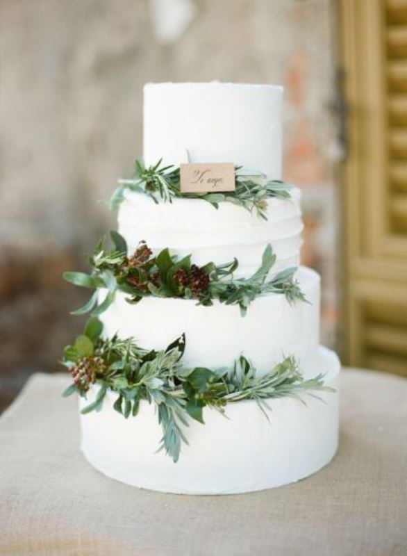 a white textural wedding cake decorated with greenery, berries and a little wedding sign will fit a modern rustic wedding