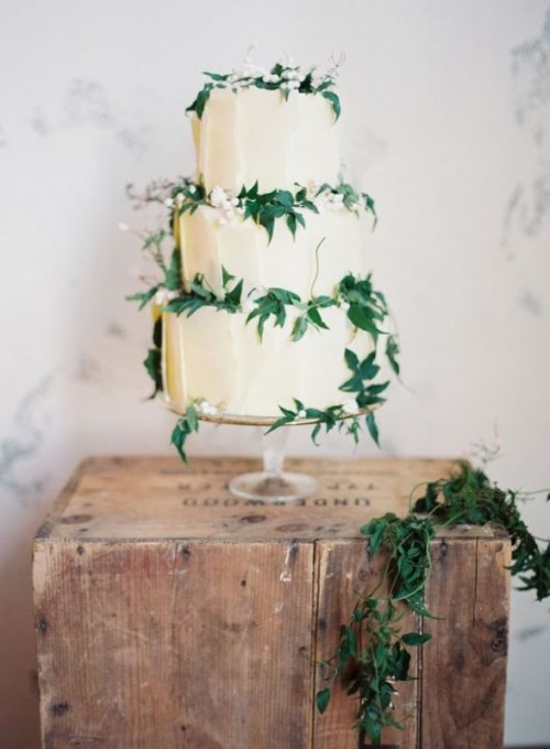 a tan textural wedding cake decorated with foliage and neutral berries is a chic idea for a garden wedding