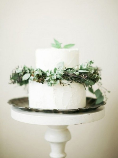a white textural wedding cake decorated with various greenery and leaves is ideal for a woodland wedding