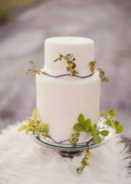 a white minimalist wedding cake with foliage and berries is a chic idea for an elegant modern wedding