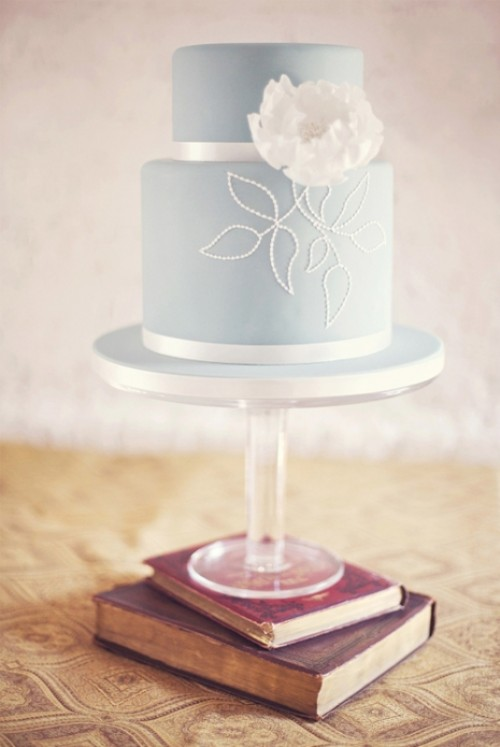 a beautiful powder blue wedding cake with white decor and a large sugar bloom is a tender and sweet idea to try
