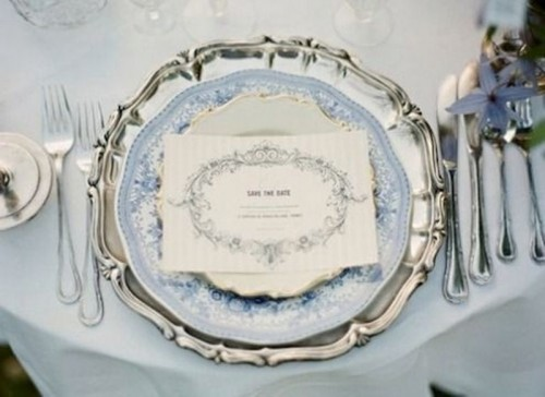 an elegant powder blue wedding place setting with a silver charger, chic cutlery and a powder bue tablecloth on the table