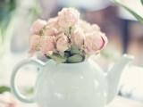 a vintage bridal shower centerpiece of a mint tea pot with pastel blooms