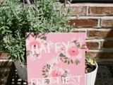 a pink floral sign is a fun and easy decor idea for a tea party bridal shower