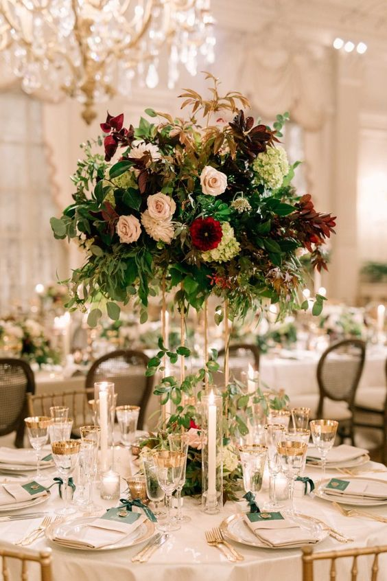 a bold and lush floral wedding centerpiece in blush, burgundy and green blooms and foliage of various shades