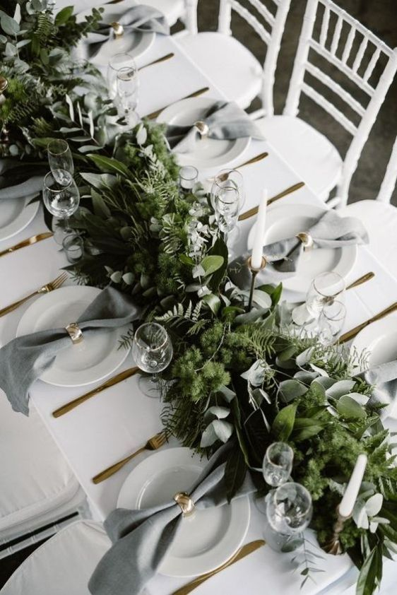 a chic neutral winter wedding tablescape with a super lush greenery runner with much texture, white porcelain, grey napkins and gold napkin rings