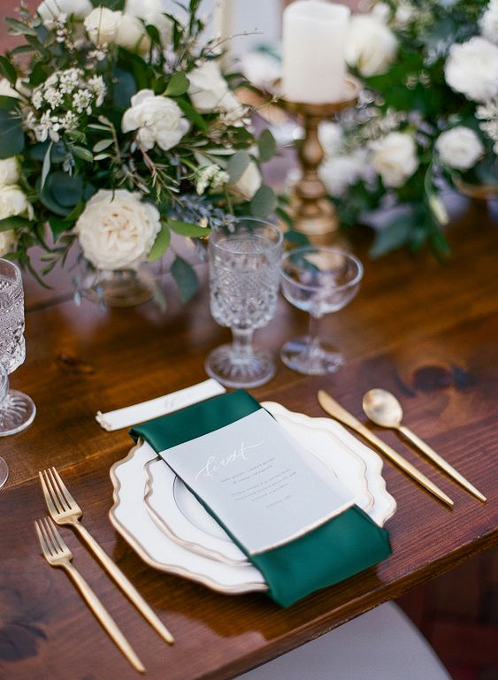 a chic winter wedding table setting with emerald napkins, gold cutlery, chic glasses and lush white bloom and greenery centerpieces