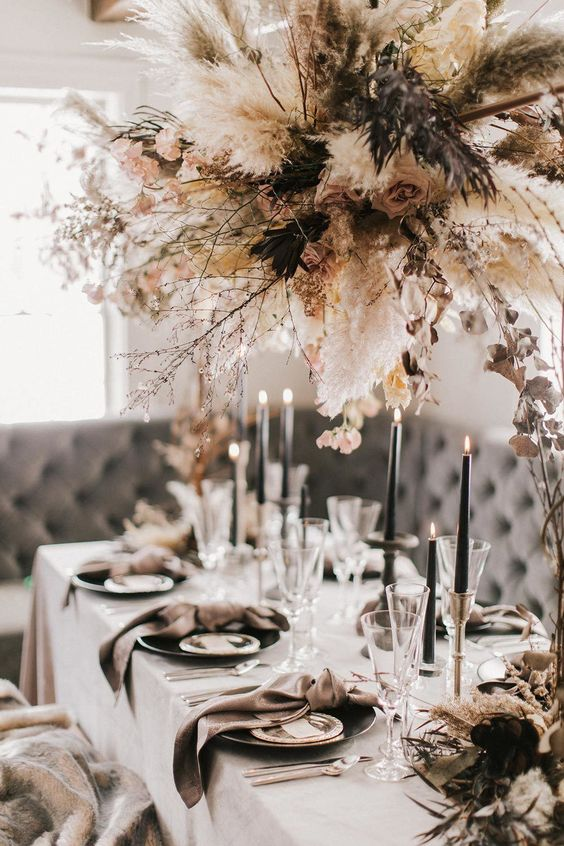 a chic winter wedding table with mauve napkins, black candles and all whites plus a large and chic dried bloom and herb overhead decoration