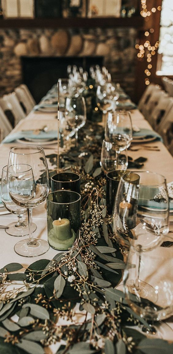 a chic winter wedding table with mint napkins, a eucalyptus runner and candles in green glass candleholders
