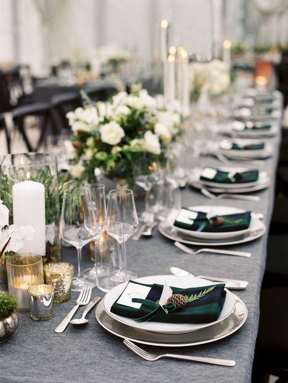 a chic winter wedding table with plaid napkins, white floral centerpieces and greenery, lots of candles and chic cutlery