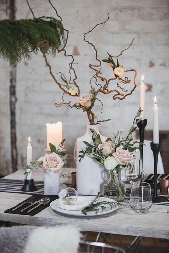 a chic winter wedding tablescape with blush blooms, branches, candles, black candleholders and napkins