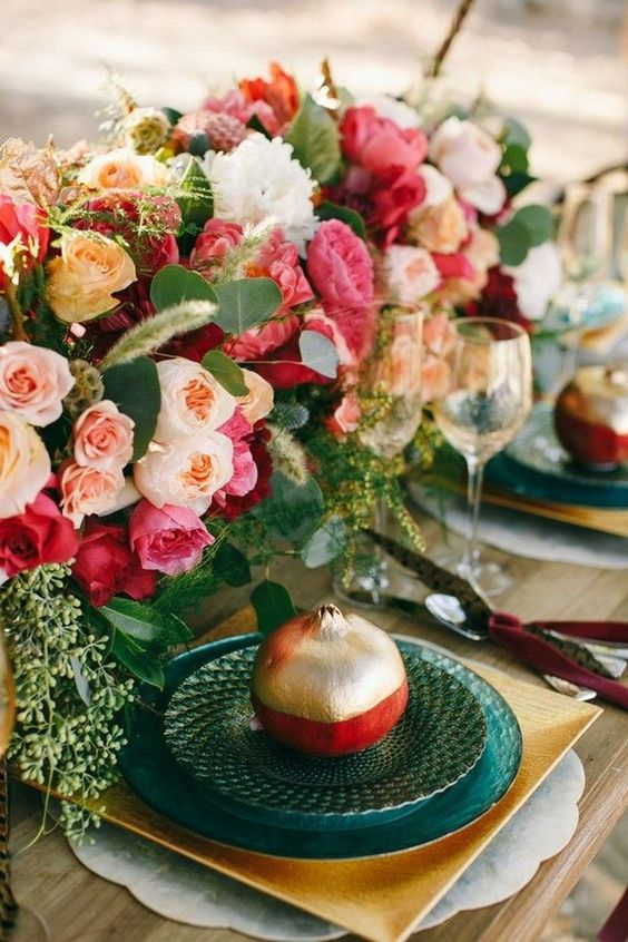 a colorful wedding tablescape with lush blush, pink and peachy blooms, greenery, green and gold plates and color block pomegranates