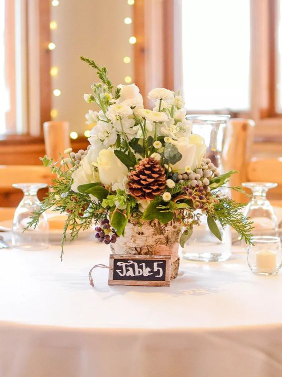 a cozy and rustic winter wedding centerpiece of a tree stump, greenery and evergreens, white blooms, berries and pinecones