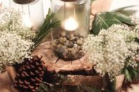 a cozy rustic centerpiece of pebbles, evergreens, pinecones, candles and little white blooms