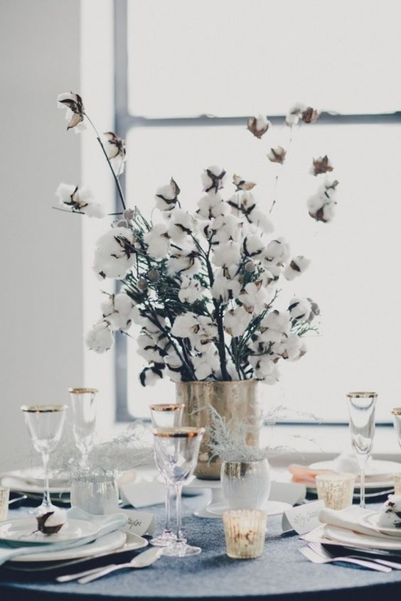 a cozy winter wedding centerpiece of a shiny vase and cotton branches is all you need for a homey feel