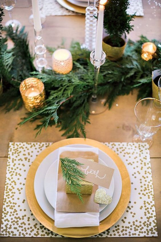 a festive winter wedding tablescape with evergreens, candles, polka dot placemats and gold chargers
