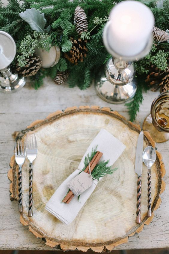 a gorgeous rustic table with a wood slcie placemat, cinnamon and evergreens, pinecones and pale foliage plus candles