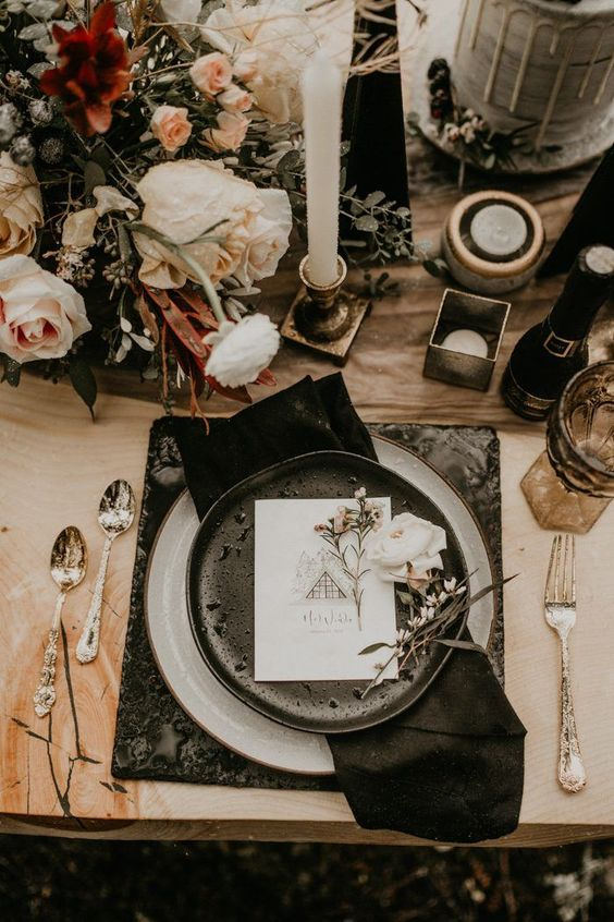 a moody winter wedding tablescape with elegant cutlery, black plates and placemats, gold candleholders and blush and burgundy blooms