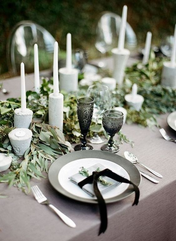 a natural winter wedding table in grey and greens, concrete candleholders, black glasses and grey plates and black ribbons