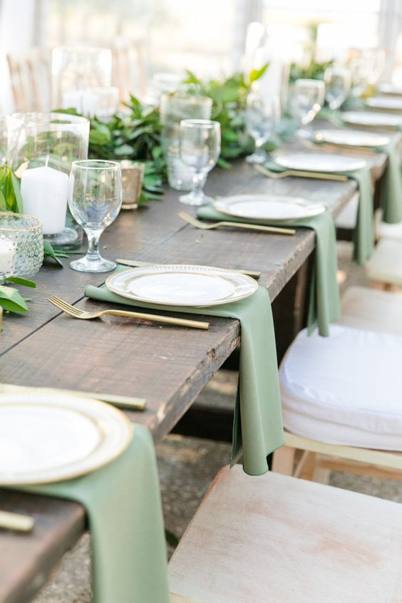 a natural winter wedding table with a greenery runner, candles, green napkins, gold cutlery