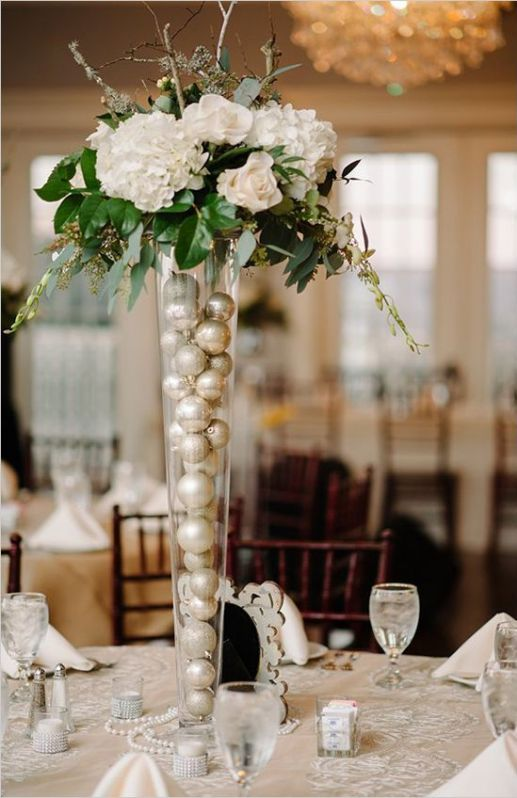 a neutral holiday centerpiece of metallic ornaments in a tall vase, foliage and white blooms plus branches