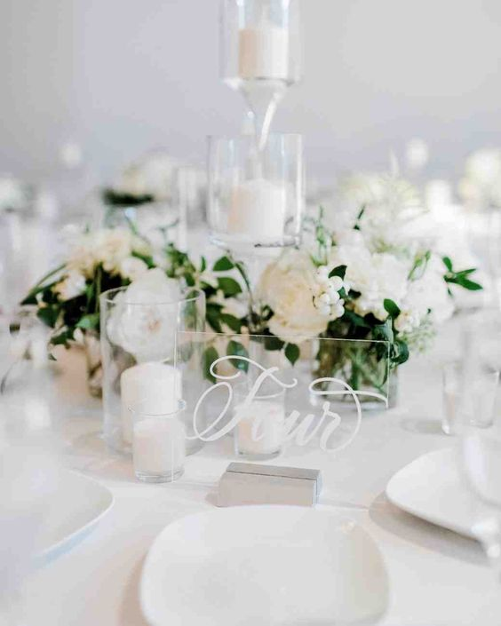a pure white winter wedding centerpiece of blooms and berries, pillar candles and an acrylic table number