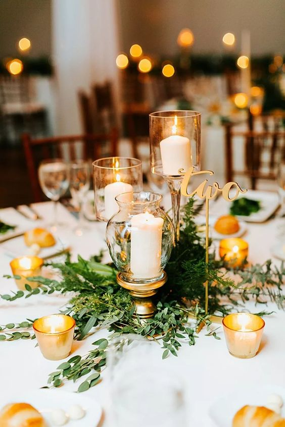 a refined winter wedding centerpiece of fresh greenery, pillar candles in candleholders, candles and a gold table number