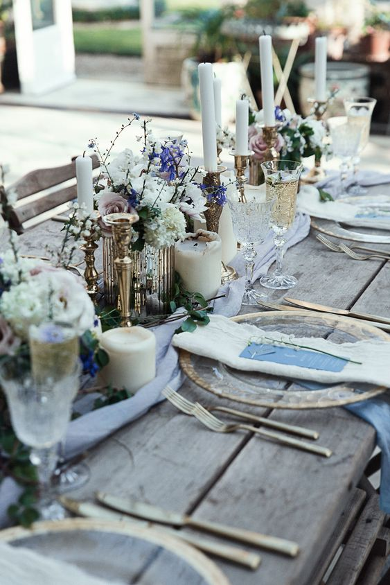 a rough winter wedding table with an uncovered table, pillar candles, white and purple blooms, twigs and refined glasses