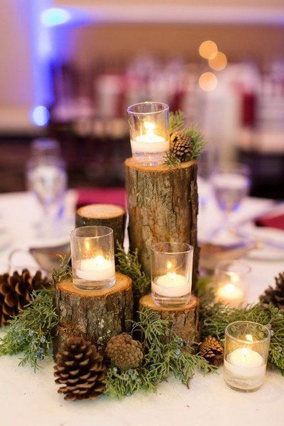 a rustic winter wedding centerpiece of evergreens, pinecones, tree stumps and mini candles