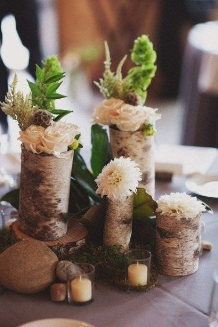 a rustic winter wedding centerpiece of wood slices, tree stumps, candles, pebbles and some greenery and blooms