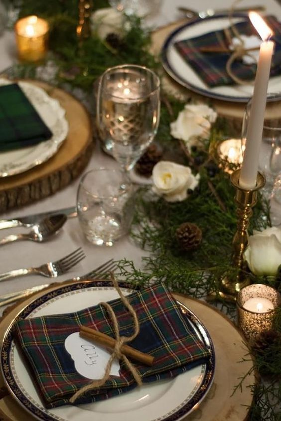 a rustic winter wedding table setting with plaid napkins, cinnamon, evergreens, white blooms and pinecones