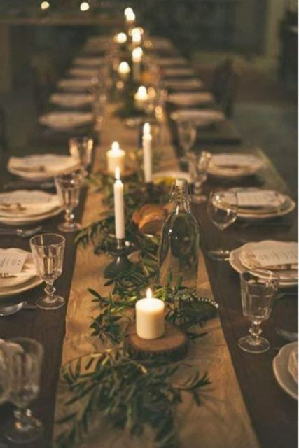 a rustic winter wedding tablescape with a fabric runner, greenery, candles and some wood slices