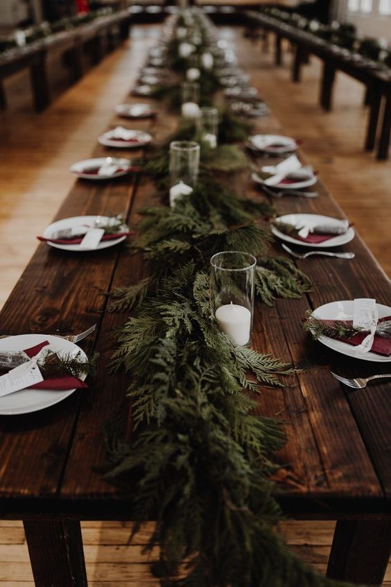 a rustic winter wedding tablescape with an uncovered table, burgundy napkins, an evergreen runner and candles in glasses