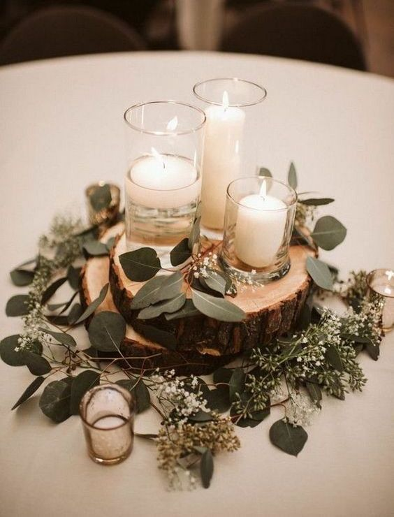 a simple and cozy rustic winter wedding centerpiece of wood slices, eucalyptus, candles in candleholders