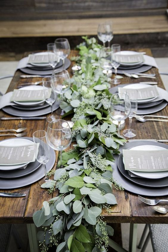a simple and neutral winter wedding tablescape with grey plates, a eucalyptus runner, grey menus and elegant cutlery