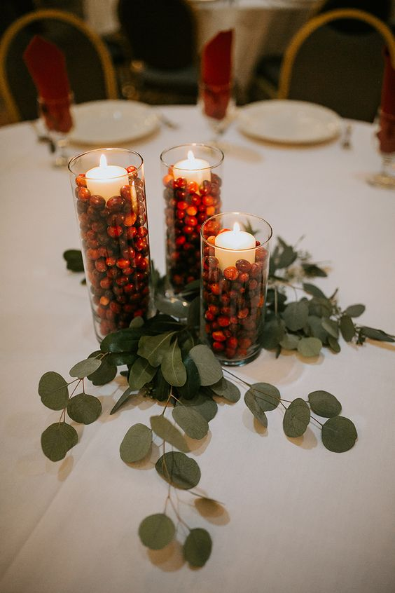 a simple winter wedding centerpiece of eucalyptus, cranberries and pillar candles in tall glasses looks bold and chic