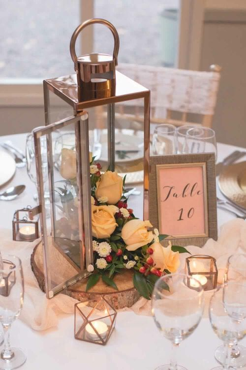 a simple winter wedding centerpiece of white blooms, cranberries in a lantern plus a table number