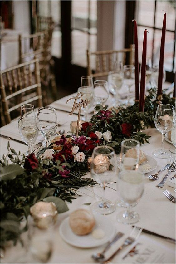 a stylish and lush winter wedding table with a refined floral and greeneryrunner, burgundy candles, mercury glass and an elegant table number