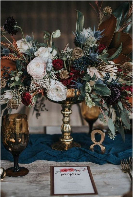 a stylish and textural winter floral centerpiece of burgundy, blush blooms, thistles, privet berries and foliage