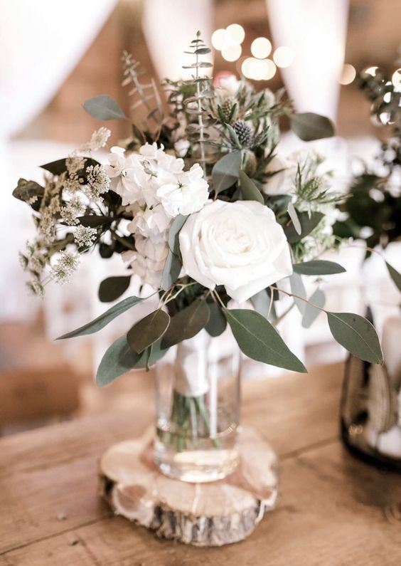 a stylish winter wedding centerpiece of white blooms, greenery and thistles always works for any wedding