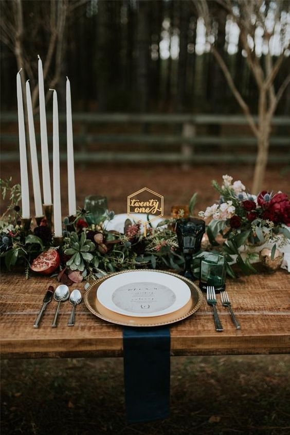 a stylish winter wedding table with a lush greenery, suculent, burgundy blooms runner, candles and pomegranates