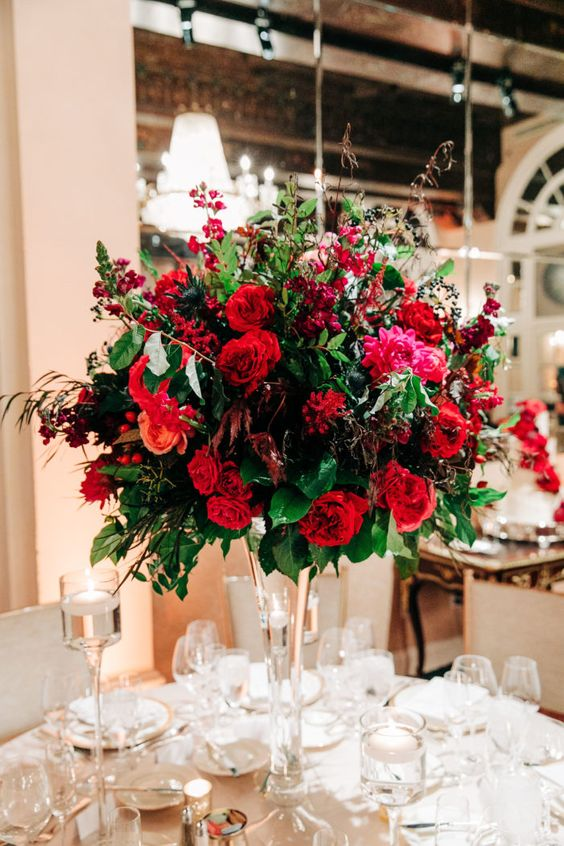 a super bright holiday wedding centerpiece with red and fuchsia blooms, foliage and berries