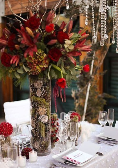 a whimsy winter wedding centerpiece of a tall vase with moss and pinecones and moody blooms for a cool look