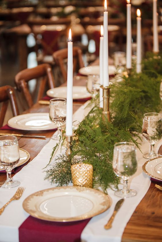 a winter holiday wedding table with pine, gilded plates and candleholders, burgundy napkins and thin and tall candles