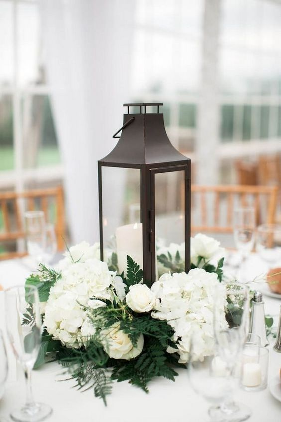 a winter wedding centerpiece of white blooms and a candle lantern plus ferns around