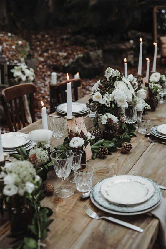 a woodland winter wedding table with an uncovered table, a greenery and white bloom runner, pinecones, white candles and printed plates