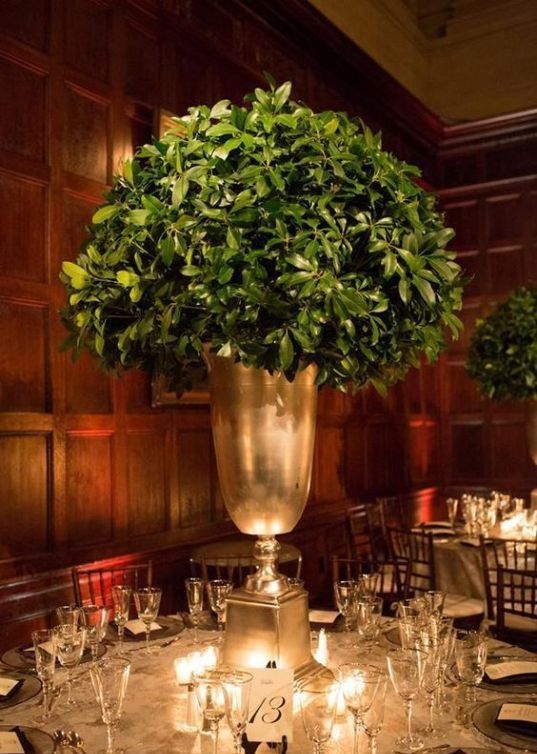 an elegant winter wedding centerpiece of a metallic urn with much greenery in it is a stylish idea